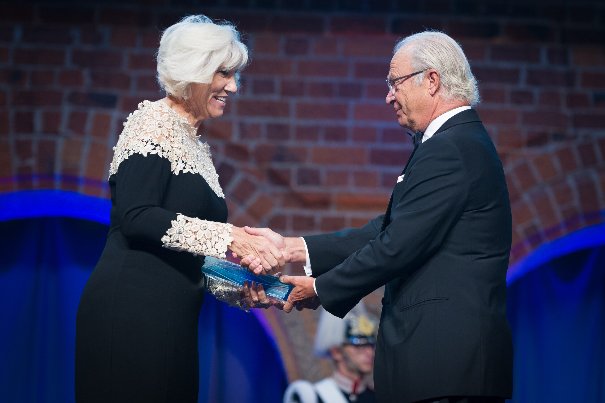 Profile view of Joan Rose accepting the Stockholm Prize and shaking hands with the award distributor.