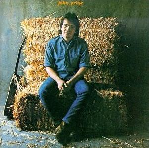 Album cover depicts John Prine sitting on a bale of hay next to his guitar, smiling at the camera.