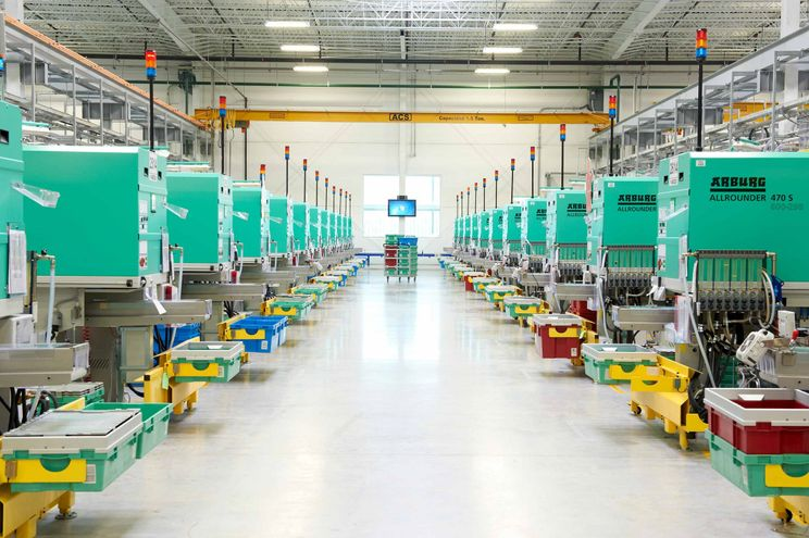 A wide view of the inside of a LEGO manufacturing plant shows rows of machinery.