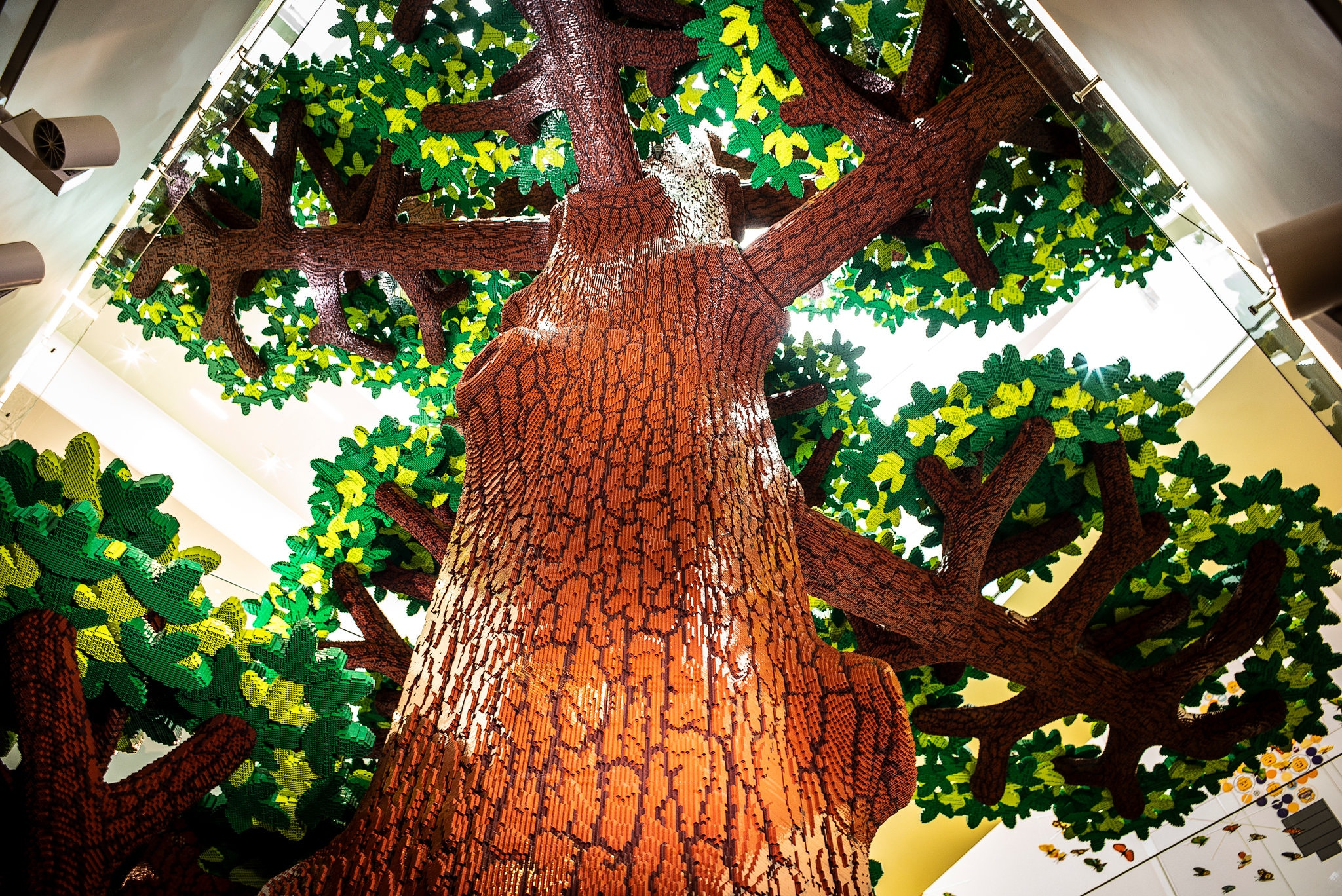 A massive semi-realistic tree built entirely of LEGO bricks, seen from an on-the-ground vantage point.