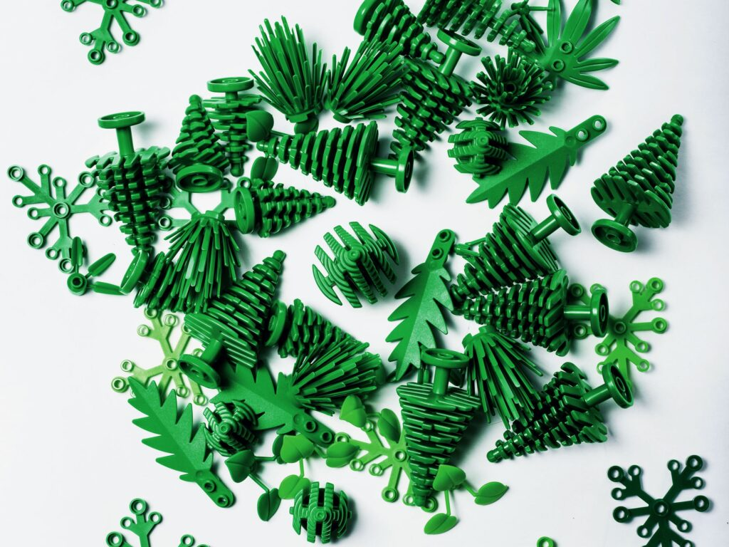 LEGO's new sugarcane-based plastic pieces, colored green and shaped like trees, shrubs, and other greenery, are scattered on a white background.