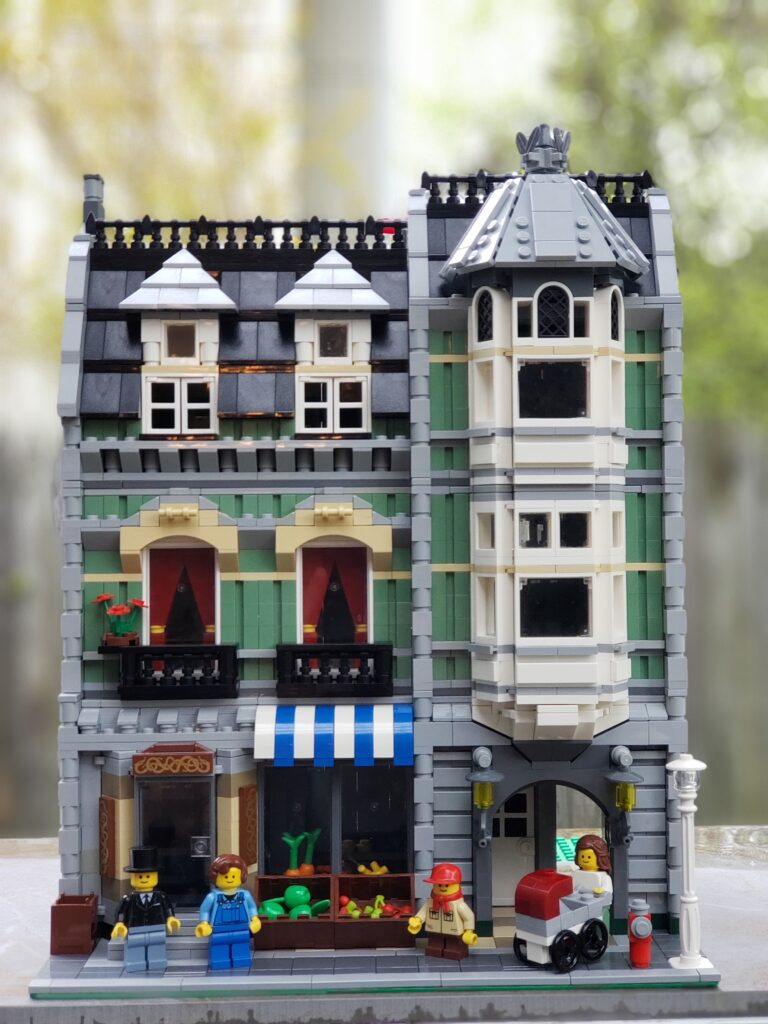 The LEGO Green Grocer set consists of a quaint three-story LEGO building populated with tiny civilians dressed in period clothing.