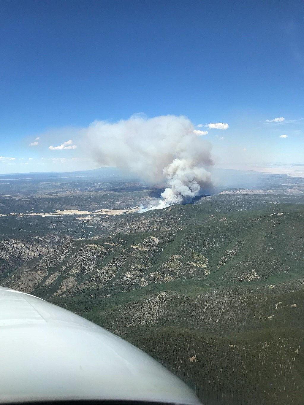 Seen from an airplane window, a plume of white smoke billows from the burn zone down below.